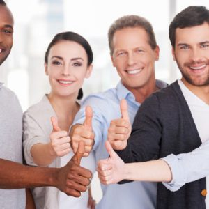 Group of cheerful business people in casual wear standing close to each other and showing their thumbs up